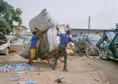 Deux Wecyclers relèvent leur triporteur trop lourdement chargé. Les déchets sont ramenés dans un des 3 hubs de la PME à Lagos où ils sont à nouveau triés avant d'être revendus. Joan Bardeletti