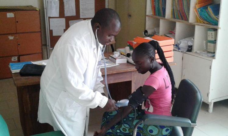 Un infirmier consulte une patiente à Dielmo au Sénégal où est installé le POC (petit laboratoire au chevet du malade).